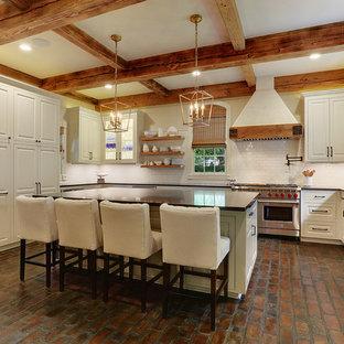 Große Landhausstil Küche in U-Form mit Vorratsschrank, Unterbauwaschbecken, Kassettenfronten, weißen Schränken, Granit-Arbeitsplatte, Küchenrückwand in Weiß, Küchengeräten aus Edelstahl, Backsteinboden, Kücheninsel und Rückwand aus Metrofliesen in New Orleans