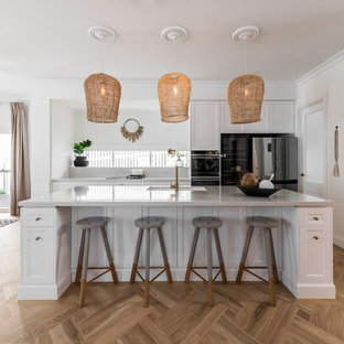 Inspiration for a large beach style galley eat-in kitchen in Brisbane with an undermount sink, marble benchtops, white splashback, marble splashback, with island, white benchtop, recessed-panel cabinets, white cabinets, black appliances, medium hardwood floors and beige floor.
