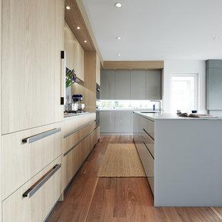 Modelo de cocina en L, actual, de tamaño medio, abierta, con fregadero bajoencimera, armarios con paneles lisos, puertas de armario de madera clara, suelo de madera oscura, una isla, encimera de vidrio, salpicadero verde y electrodomésticos de acero inoxidable