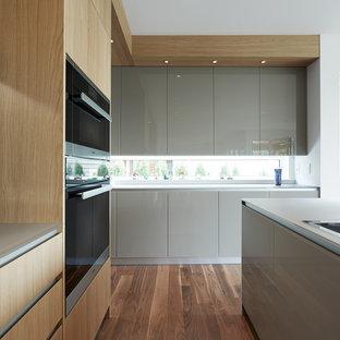 Offene, Mittelgroße Moderne Küche in L-Form mit Unterbauwaschbecken, flächenbündigen Schrankfronten, hellen Holzschränken, Glas-Arbeitsplatte, Küchenrückwand in Grau, Küchengeräten aus Edelstahl, dunklem Holzboden und Kücheninsel in Vancouver