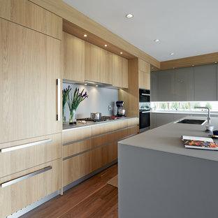 Новый формат декора квартиры: угловая кухня-гостиная среднего размера в современном стиле с врезной раковиной, плоскими фасадами, светлыми деревянными фасадами, стеклянной столешницей, серым фартуком, техникой из нержавеющей стали, паркетным полом среднего тона и островом