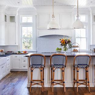 チャールストンの広いビーチスタイルのおしゃれなキッチン (エプロンフロントシンク、ソープストーンカウンター、白いキッチンパネル、磁器タイルのキッチンパネル、無垢フローリング、茶色い床、黒いキッチンカウンター、白いキャビネット、シェーカースタイル扉のキャビネット) の写真