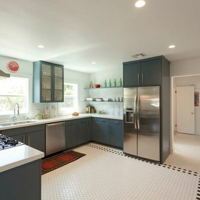 Eclectic u-shaped enclosed kitchen photo in Los Angeles with blue cabinets, white backsplash, subway tile backsplash and stainless steel appliances