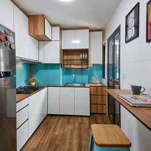 シンガポールの小さいコンテンポラリースタイルのおしゃれなL型キッチン (シングルシンク、フラットパネル扉のキャビネット、白いキャビネット、木材カウンター、青いキッチンパネル、ガラス板のキッチンパネル、無垢フローリング、アイランドなし) の写真