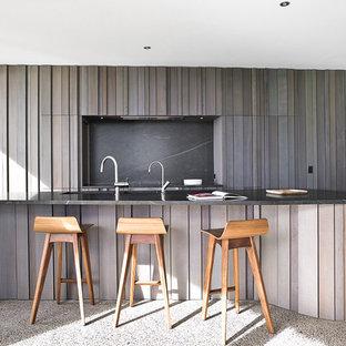 Imagen de cocina contemporánea con puertas de armario de madera oscura, encimera de granito, salpicadero negro, electrodomésticos de acero inoxidable, fregadero bajoencimera, armarios con rebordes decorativos, suelo de terrazo, una isla y suelo gris