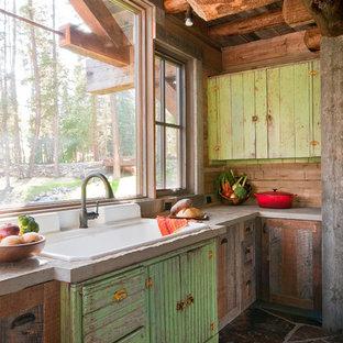 Foto på ett rustikt kök, med bänkskiva i betong, en nedsänkt diskho och skåp i slitet trä