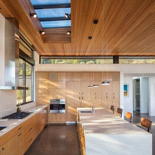 Ispirazione per una grande cucina abitabile minimalista con ante lisce, ante in legno chiaro, top in cemento, elettrodomestici in acciaio inossidabile, pavimento in cemento, isola e lavello a doppia vasca