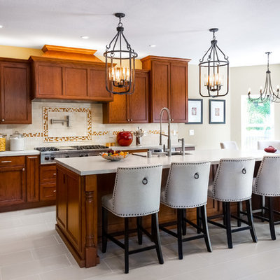 Inspiration for a large timeless l-shaped porcelain tile and beige floor eat-in kitchen remodel in San Francisco with an undermount sink, recessed-panel cabinets, medium tone wood cabinets, quartz countertops, beige backsplash, stone tile backsplash, stainless steel appliances, an island and beige countertops