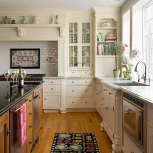 Elegant l-shaped light wood floor eat-in kitchen photo in Boston with an undermount sink, flat-panel cabinets, white cabinets, stainless steel appliances and white backsplash