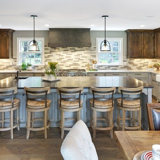 This is an example of a large country u-shaped eat-in kitchen in Minneapolis with a farmhouse sink, recessed-panel cabinets, grey cabinets, multi-coloured splashback, panelled appliances, with island, solid surface benchtops, brown floor, porcelain splashback and medium hardwood floors.