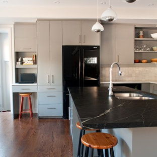 Moderne Wohnküche mit Doppelwaschbecken, schwarzen Elektrogeräten, Speckstein-Arbeitsplatte, flächenbündigen Schrankfronten, grauen Schränken, Küchenrückwand in Weiß und Rückwand aus Steinfliesen in Toronto
