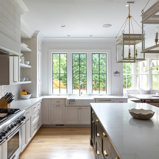 Farmhouse eat-in kitchen inspiration - Eat-in kitchen - cottage l-shaped light wood floor and beige floor eat-in kitchen idea in Charlotte with a farmhouse sink, shaker cabinets, white cabinets, white backsplash, stainless steel appliances, an island and white countertops