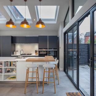 Medium sized contemporary kitchen in Manchester with a submerged sink, flat-panel cabinets, white splashback, porcelain splashback, ceramic flooring, grey floors, grey cabinets, black appliances and an island.