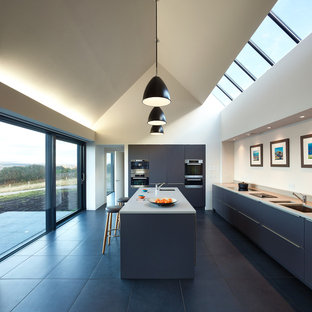 Ispirazione per una cucina ad U contemporanea con lavello a doppia vasca, ante lisce, ante blu, elettrodomestici neri, isola, pavimento nero e top grigio