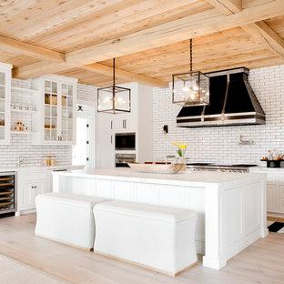 Inspiration för ett mycket stort vintage l-kök, med skåp i shakerstil, vita skåp, vitt stänkskydd, stänkskydd i tunnelbanekakel, rostfria vitvaror, ljust trägolv, en köksö, beiget golv, bänkskiva i kvarts och en rustik diskho