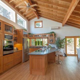 Cette photo montre une cuisine américaine bord de mer en U avec un placard à porte shaker, des portes de placard en bois brun, un sol en bois brun et un îlot central.