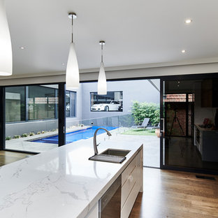 Inspiration for a large modern single-wall eat-in kitchen in Melbourne with an undermount sink, louvered cabinets, medium wood cabinets, marble benchtops, white splashback, stone slab splashback, stainless steel appliances, medium hardwood floors, with island, brown floor and white benchtop.