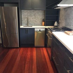 メルボルンの小さいコンテンポラリースタイルのおしゃれなキッチン (アンダーカウンターシンク、シェーカースタイル扉のキャビネット、グレーのキャビネット、クオーツストーンカウンター、グレーのキッチンパネル、モザイクタイルのキッチンパネル、シルバーの調理設備の、無垢フローリング、赤い床、白いキッチンカウンター、アイランドなし) の写真