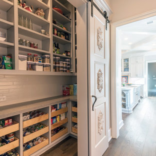 Photo of a large traditional l-shaped kitchen pantry in Houston with open cabinets, grey cabinets, dark hardwood floors and brown floor.