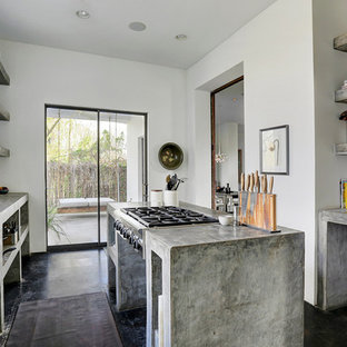 Mid-sized southwestern enclosed kitchen designs - Mid-sized southwest concrete floor enclosed kitchen photo in Houston with an undermount sink, open cabinets, gray cabinets, concrete countertops, stainless steel appliances and an island