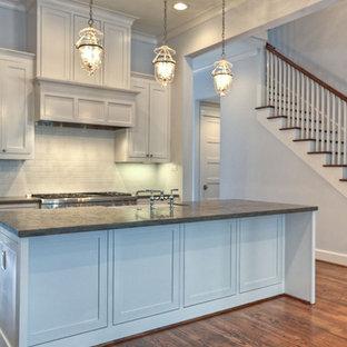 ヒューストンの中サイズのヴィクトリアン調のおしゃれなキッチン (ドロップインシンク、落し込みパネル扉のキャビネット、白いキャビネット、珪岩カウンター、白いキッチンパネル、サブウェイタイルのキッチンパネル、白い調理設備、無垢フローリング) の写真