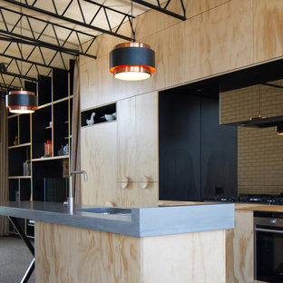 This is an example of an urban single-wall open plan kitchen in Melbourne with a submerged sink, flat-panel cabinets, light wood cabinets, stainless steel appliances, an island, concrete worktops, mirror splashback and concrete flooring.