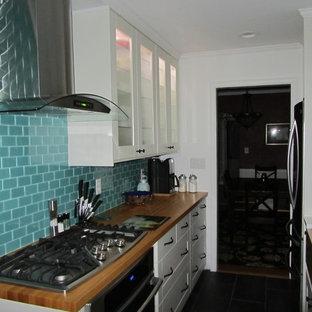 Ejemplo de cocina de galera, minimalista, pequeña, con armarios tipo vitrina, puertas de armario blancas, encimera de madera, salpicadero azul, salpicadero de azulejos de vidrio, electrodomésticos de acero inoxidable y suelo de baldosas de porcelana