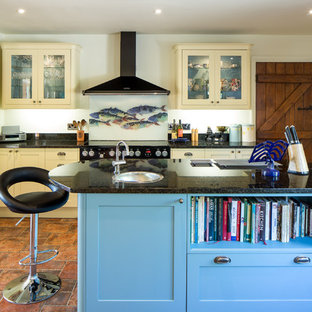 Medium sized country u-shaped open plan kitchen in Hertfordshire with a built-in sink, shaker cabinets, blue cabinets, granite worktops, white splashback, brick splashback, white appliances, ceramic flooring, an island and brown floors.