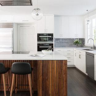 Idée de décoration pour une cuisine tradition en L avec un évier encastré, un placard à porte plane, des portes de placard blanches, une crédence grise, un sol en bois foncé, un îlot central et un sol marron.