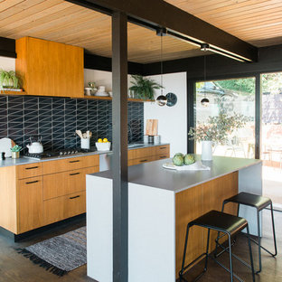 Inspiration for a midcentury kitchen in San Francisco with flat-panel cabinets, medium wood cabinets, black splashback, dark hardwood floors, with island, brown floor and white benchtop.