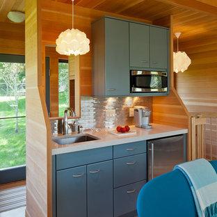 Rustik inredning av ett litet kök, med en undermonterad diskho, släta luckor, blå skåp, bänkskiva i kvarts, stänkskydd med metallisk yta, stänkskydd i metallkakel, rostfria vitvaror och ljust trägolv