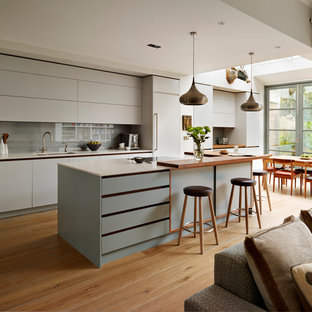 Inspiration for a large contemporary galley open plan kitchen in London with flat-panel cabinets, composite countertops, grey splashback, stainless steel appliances, an island, white worktops, a submerged sink, grey cabinets, glass sheet splashback, medium hardwood flooring and brown floors.