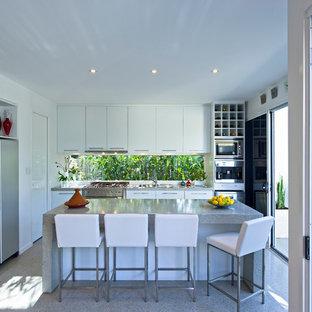 Imagen de cocina en L, contemporánea, de tamaño medio, abierta, con armarios con paneles lisos, puertas de armario blancas, electrodomésticos de acero inoxidable, una isla y suelo de terrazo