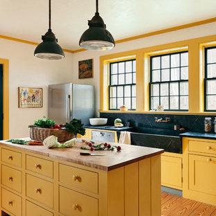 ニューヨークの中サイズのカントリー風おしゃれなアイランドキッチン (エプロンフロントシンク、黄色いキャビネット、ソープストーンカウンター、黒いキッチンパネル、石スラブのキッチンパネル、シルバーの調理設備の、黒いキッチンカウンター、インセット扉のキャビネット、淡色無垢フローリング) の写真