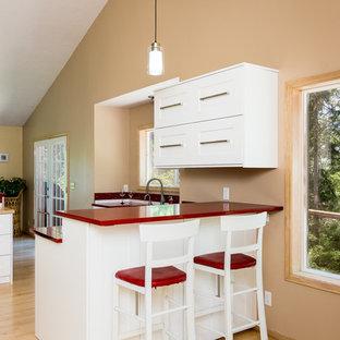 На фото: угловая кухня среднего размера в классическом стиле с обеденным столом, врезной раковиной, фасадами в стиле шейкер, белыми фасадами, столешницей из кварцевого агломерата, красным фартуком, фартуком из стекла, техникой из нержавеющей стали, светлым паркетным полом, островом, коричневым полом и красной столешницей с