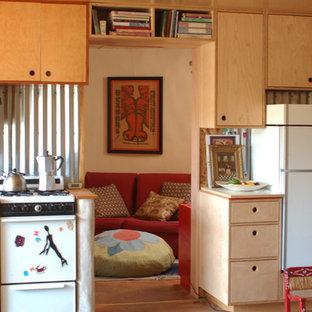 アルバカーキの小さいシャビーシック調のおしゃれなキッチン (ダブルシンク、フラットパネル扉のキャビネット、淡色木目調キャビネット、ステンレスカウンター、メタリックのキッチンパネル、コンクリートの床、アイランドなし) の写真
