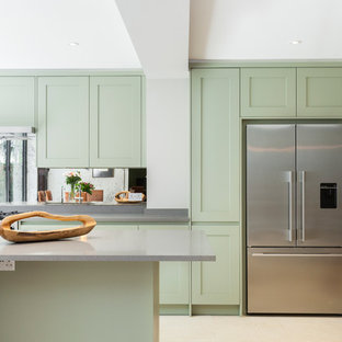 Inspiration for a traditional kitchen in London with a submerged sink, shaker cabinets, green cabinets, metallic splashback, stainless steel appliances and an island.