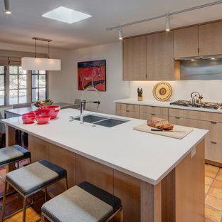 アルバカーキの中くらいのエクレクティックスタイルのおしゃれなキッチン (アンダーカウンターシンク、フラットパネル扉のキャビネット、淡色木目調キャビネット、クオーツストーンカウンター、白いキッチンパネル、磁器タイルのキッチンパネル、シルバーの調理設備、テラコッタタイルの床、オレンジの床、白いキッチンカウンター) の写真