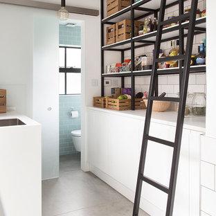 Modelo de cocina de galera, contemporánea, pequeña, sin isla, con armarios con paneles lisos, puertas de armario blancas, salpicadero blanco, salpicadero de azulejos tipo metro, encimera de acrílico, suelo de cemento y despensa