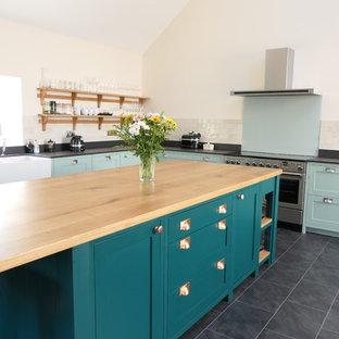 Große, Offene Klassische Küche in L-Form mit Landhausspüle, Schrankfronten im Shaker-Stil, grünen Schränken, Quarzwerkstein-Arbeitsplatte, Küchenrückwand in Grau, Glasrückwand, Küchengeräten aus Edelstahl, Keramikboden, Kücheninsel, schwarzem Boden und schwarzer Arbeitsplatte in West Midlands
