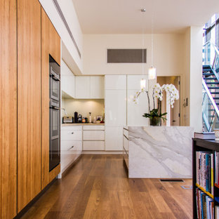 This is an example of a contemporary l-shaped kitchen in Melbourne with flat-panel cabinets, white cabinets, stainless steel appliances, medium hardwood floors, with island, brown floor and grey benchtop.