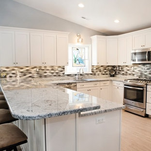 This is an example of a mid-sized contemporary u-shaped open plan kitchen in Baltimore with an undermount sink, shaker cabinets, white cabinets, granite benchtops, glass tile splashback, stainless steel appliances, vinyl floors, with island, grey benchtop, multi-coloured splashback and beige floor.