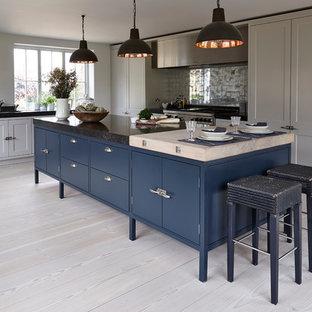 Klassisk inredning av ett l-kök, med grå skåp, stänkskydd med metallisk yta, rostfria vitvaror, ljust trägolv och en köksö