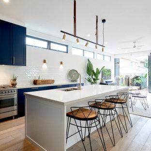 Esempio di una cucina minimal con lavello sottopiano, ante in stile shaker, ante nere, paraspruzzi bianco, elettrodomestici in acciaio inossidabile, pavimento in legno massello medio, isola, pavimento marrone e top bianco