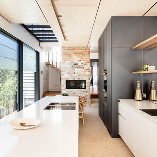 Design ideas for a contemporary galley eat-in kitchen in Sydney with a drop-in sink, flat-panel cabinets, grey cabinets, window splashback, concrete floors, with island, beige floor and white benchtop.