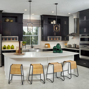 Transitional kitchen remodeling - Kitchen - transitional l-shaped gray floor kitchen idea in Jacksonville with a farmhouse sink, flat-panel cabinets, black cabinets, multicolored backsplash, stainless steel appliances, an island and white countertops