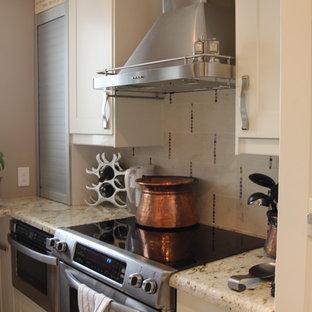オースティンの小さいエクレクティックスタイルのおしゃれなキッチン (ダブルシンク、シェーカースタイル扉のキャビネット、白いキャビネット、御影石カウンター、ベージュキッチンパネル、ガラスタイルのキッチンパネル、シルバーの調理設備の、コンクリートの床、アイランドなし、茶色い床) の写真