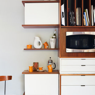 Mid-sized midcentury galley open plan kitchen in Philadelphia with flat-panel cabinets, white cabinets, wood benchtops, beige splashback, stone tile splashback, stainless steel appliances and ceramic floors.
