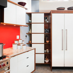 This is an example of a mid-sized midcentury galley open plan kitchen in Philadelphia with a drop-in sink, flat-panel cabinets, white cabinets, wood benchtops, beige splashback, stone tile splashback, stainless steel appliances, ceramic floors and with island.