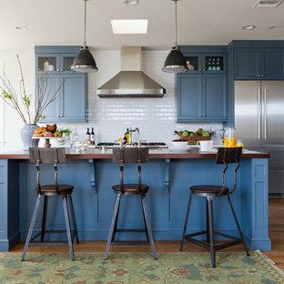 Offene, Mittelgroße Maritime Küche in L-Form mit Schrankfronten im Shaker-Stil, blauen Schränken, Arbeitsplatte aus Holz, Küchenrückwand in Weiß, Rückwand aus Keramikfliesen, Küchengeräten aus Edelstahl, braunem Holzboden und Kücheninsel in Los Angeles